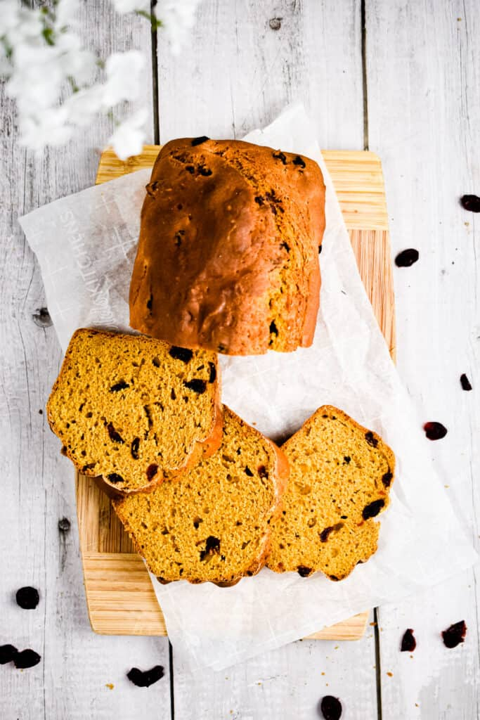 The pumpkin soda bread is on a cutting board surrounded by dried cranberries.