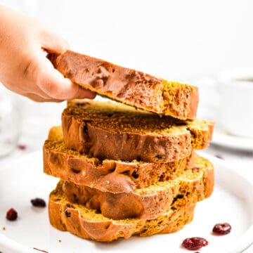 A child's hand is reaching for a stack of the pumpkin soda bread