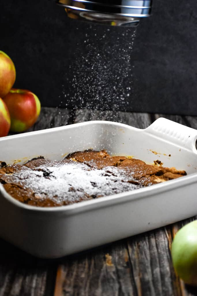 Powdered sugar is being dusted over the all in one apple cake