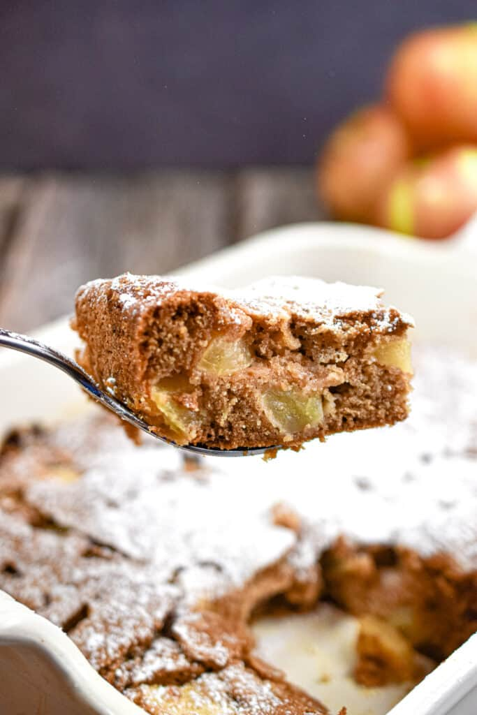 A slice of the all in one apple cake is lifted over the pan