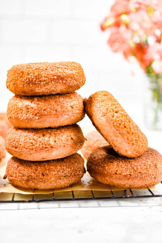 The sourdough apple cider donuts are stacked and one is leaning against the stack