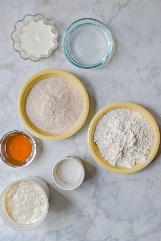 The ingredients for the sourdough dinner rolls are laid out in different sized and different color bowls.