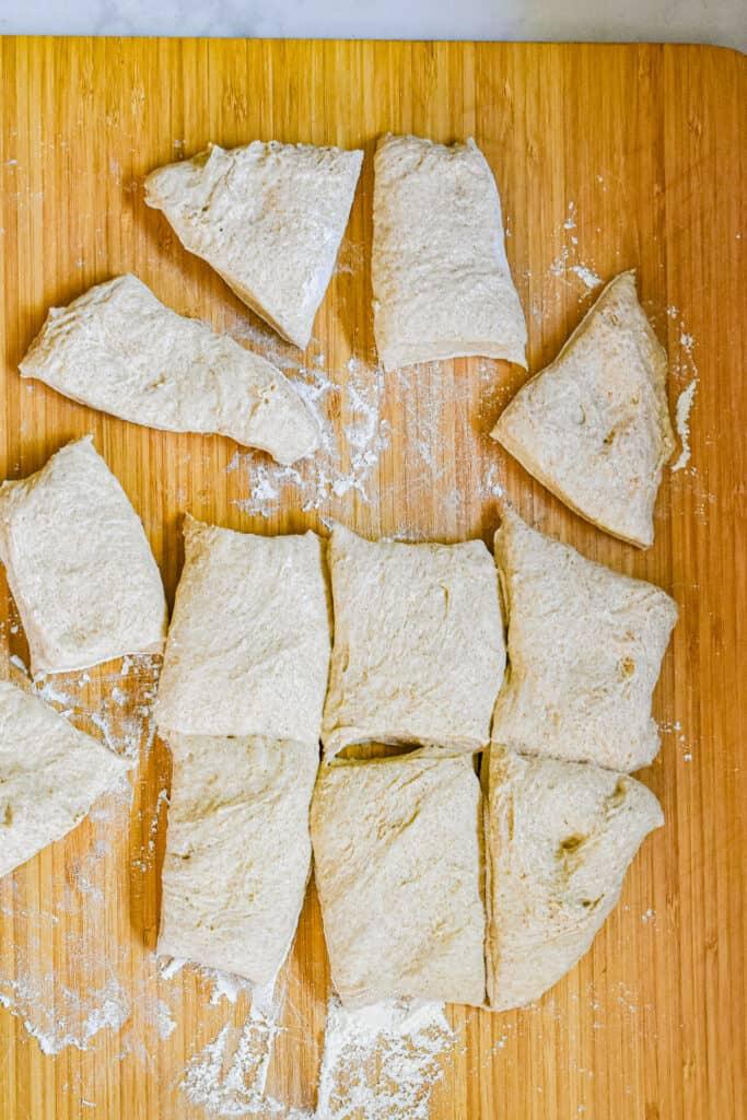 The sourdough bread roll dough is ut into 12 pieces