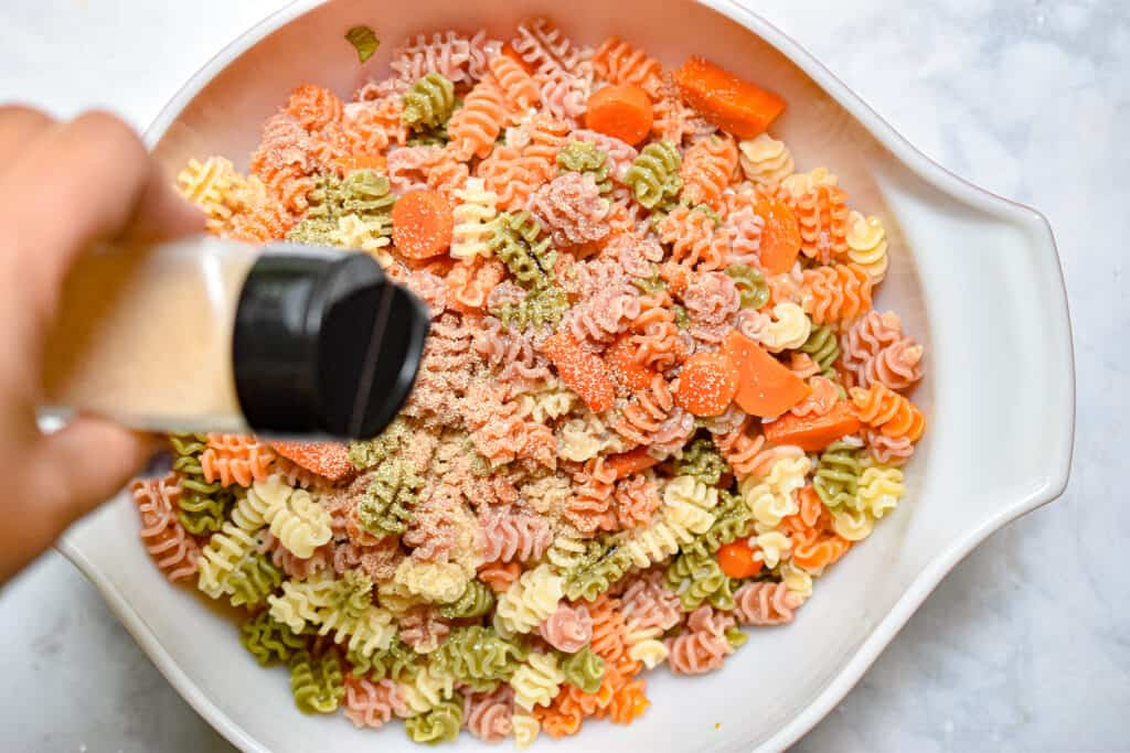 The garlic powder is being sprinkled on the pasta salad