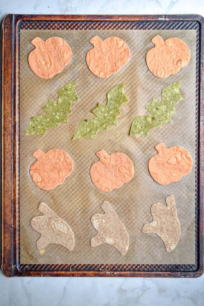 The Halloween tortilla chips are laid out on a baking sheet
