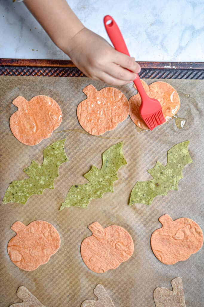 A hand is brushing oil on the tortilla cutouts