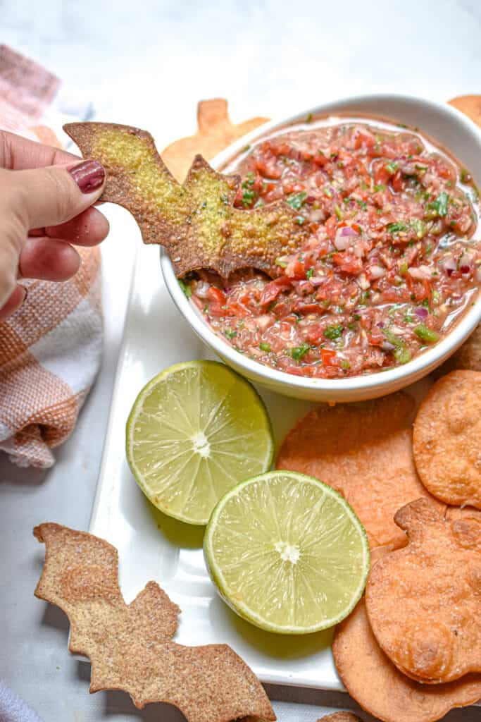 A bat tortilla chip is being dipped into a bowl of pico de gallo