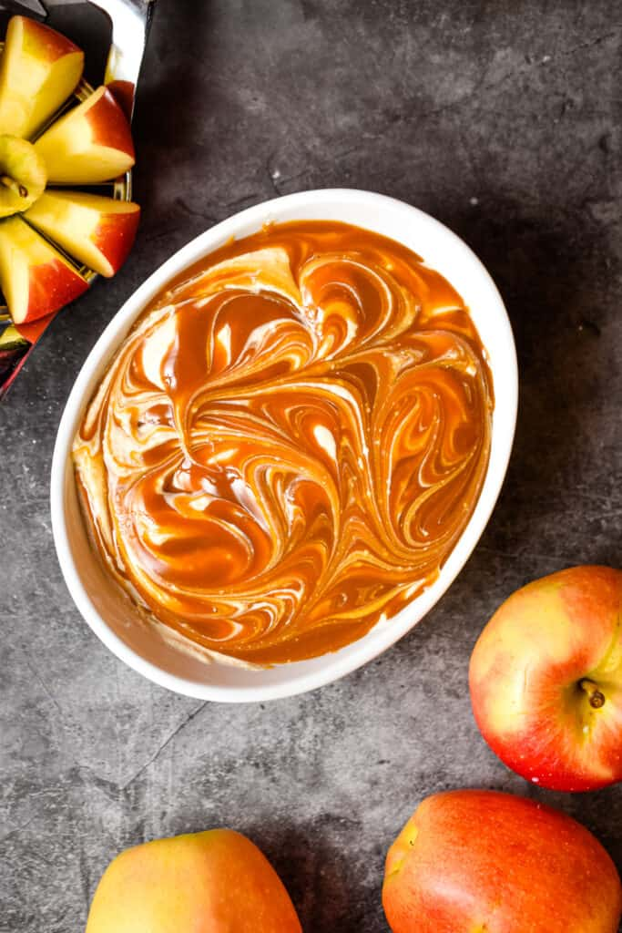 The healthy apple dip is surround by a cut apple and a whole apple