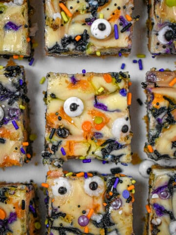 Nine Halloween Cheesecake Funfetti Bars are on a serving plate. This is a close up shot of them from above.