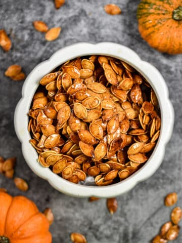 The honey roasted pumpkin seeds are in a large bowl that is surrounded by smaller pumpkin seeds